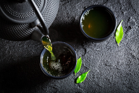 Delicious green tea with teapot and cup on black rock Stock Photo - 66654484