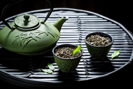 Genießen Sie Ihren Kräutertee mit Teekanne auf schwarzem Tisch