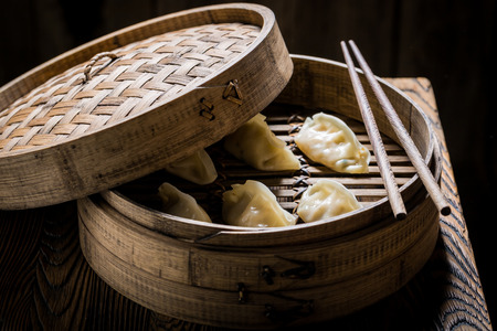 Homemade and hot chinese dumplings in wooden steamer Banco de Imagens - 66655376