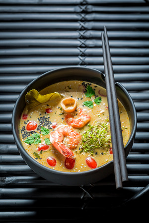 Enjoy your Tom Yum soup in black bowl with chopsticks Stock Photo