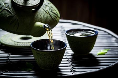 Tasty herbal tea with teapot on black table