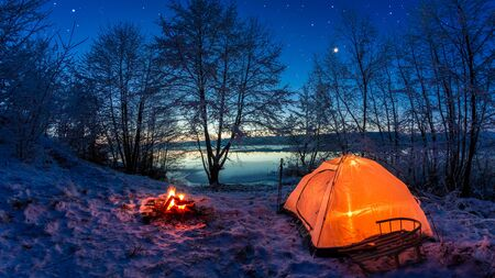 Sunrise on winter lake covered with snow at dusk Stock Photo