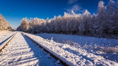Frozen railway line in winter at sunrise, Poland