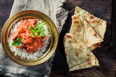 exotically: Tikka masala with rice and chicken served with Naan bread Stock Photo