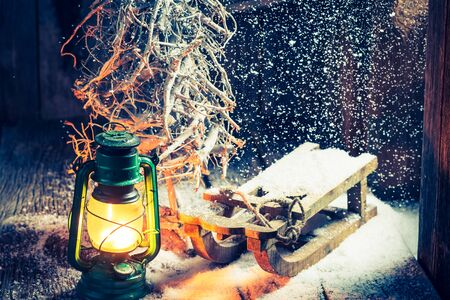 red oil lamp: Cozy winter hut with small wooden sleigh Stock Photo
