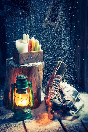 red oil lamp: Snowy winter hut with skates and wax Stock Photo