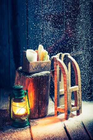 red oil lamp: Cozy winter hut with snow and oil lamp Stock Photo