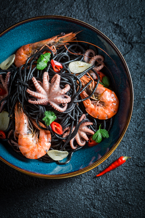 Delicious seafood black pasta made of octopus, tiger prawns Stock Photo