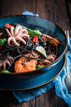 Spicy seafood black pasta with shrimp, octopus and parsley