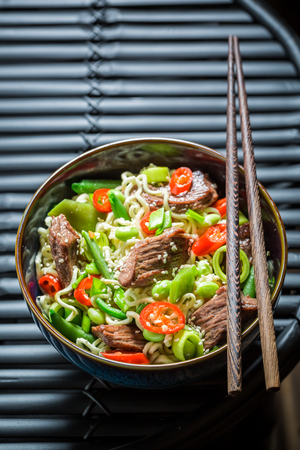 hot asian: Hot asian noodle in dark bowl with chopsticks