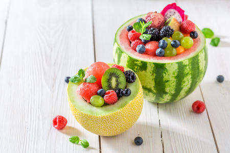 Tropical fruits salad in melon and watermelon in sunny kitchen