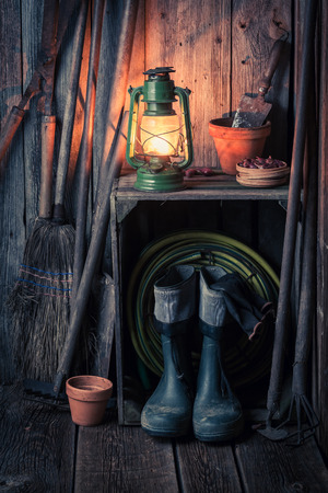 An old rustic shed with garden tools and oil lamp Stock Photo