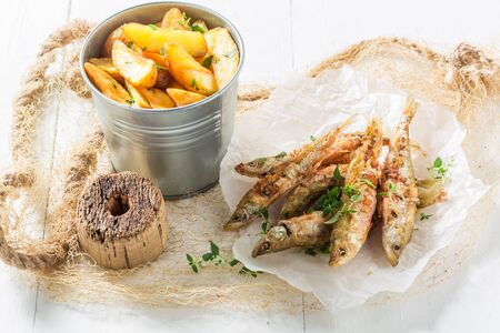 Tasty smelt fish and chips with herbs and salt Stock Photo