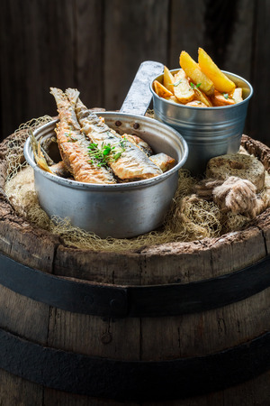 Tasty herring fish and chips with herbs and salt Stock Photo