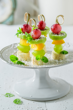 Lekkere spiesjes met verschillende soorten fruit en munt voor feest