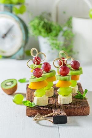 Zoete spiesjes met verschillende soorten fruit en munt voor een feestje