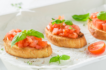Tasty bruschetta with basil and tomato for a snack Stock Photo