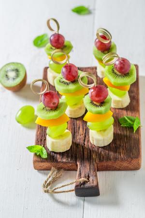 Heerlijke spiesjes met verschillende soorten fruit en munt voor een snack Stockfoto