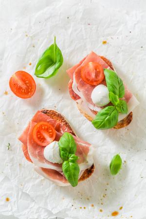 Fresh bruschetta with prosciutto, tomato and mozzarella for a snack