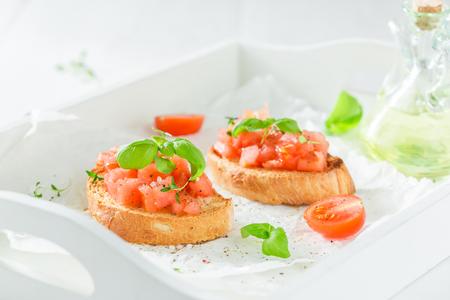 Crisp bruschetta with basil and tomato for breakfast