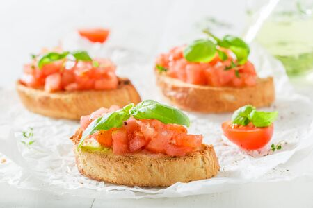 Tasty bruschetta with tomato and basil for breakfast
