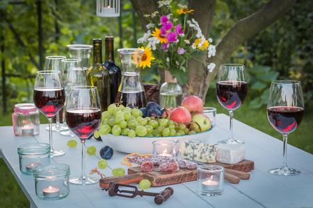 夕暮れ時の庭で軽食とワイン テーブル