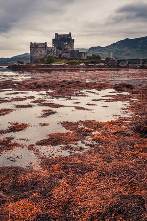 Breathtaking sunset over lake at Eilean Donan Castle in Scotland Editorial