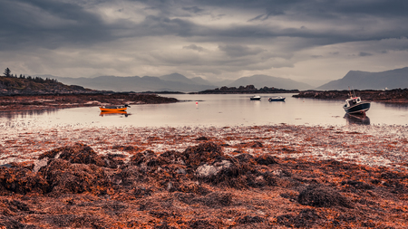 Red boats on the coast at low tide in Scotland
