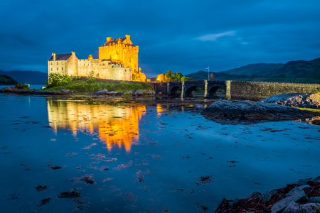 Stunning sunset over lake at Eilean Donan Castle in Scotland Editorial
