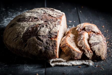 어두운 테이블에 아침 식사를 위해 건강하게 썰어 진 빵 한 덩어리
