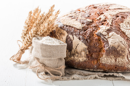 Delicious loaf of bread with whole grains on white table