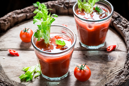 Tasty bloody mary cocktail with tomatoes and ice