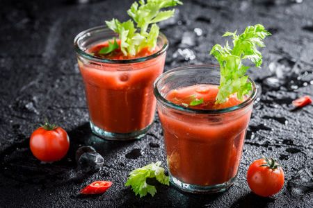 Spicy bloody mary cocktail with tomatoes and ice