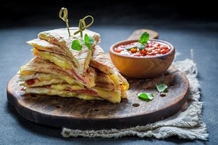 Hot tortilla as quesadilla with cheese and ham