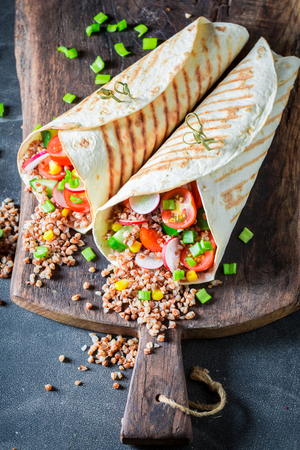 Enjoy your vegetarian tortilla with groats, cherry tomatoes and radish Stock Photo