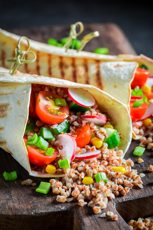 Delicious vegetarian tortilla with groats, cherry tomatoes and radish