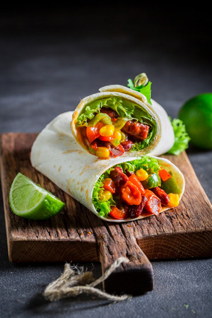 Spicy burrito with red salsa, lettuce and vegetables