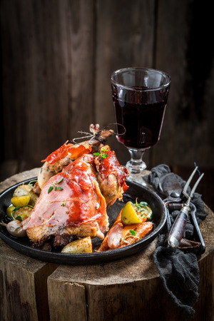 Roasted pheasant with bacon and vegetables on dark background Stock Photo