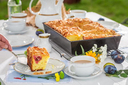 served: Sweet cake with plum served with coffee in summer garden Stock Photo