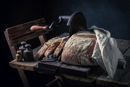 Homemade loaf of bread on old slicer