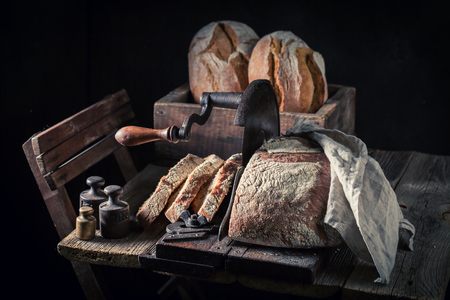 SLICER: Big loaf of bread on old wooden table Stock Photo