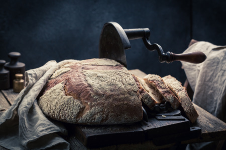 SLICER: Rustic loaf of bread in dark room