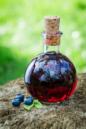 Sweet liqueur in a bottle with blueberries in summer