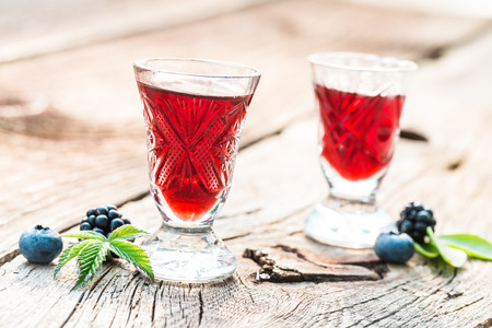 Sweet liqueur with alcohol and berry fruits in summer
