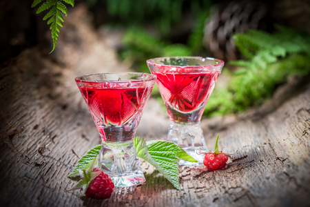 witchdoctor: Sweet raspberries liqueur made of alcohol and fruits in forest