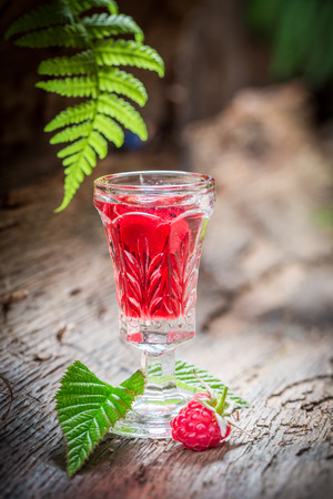 Closeup of raspberries liqueur with fruits and alcohol