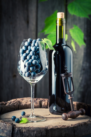 Closeup of red wine in bottle and grapes in glass