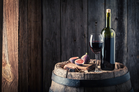 Red wine with figs on oak barrel