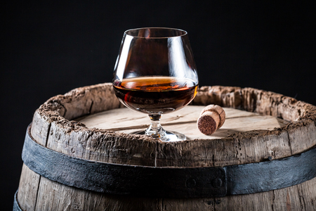 Glass of good whisky on oak barrel