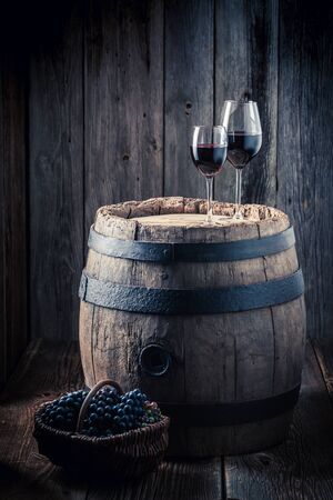 Tasty red wine and grapes and oak barrel Stock Photo